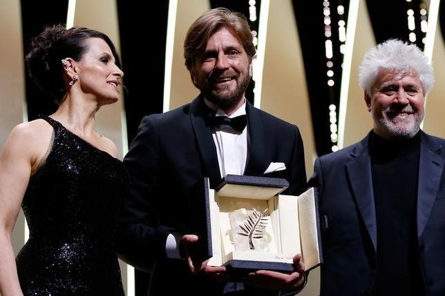 5月28日、カンヌ映画祭の授賞式が行われ、リューベン・オストルンド監督(中央)による「The Square」がコンペティション部門の最高賞「パルムドール」に輝いた。写真左は女優ジュリエット・ビノシュ、右は審査委員長のペドロ・アルモドバル監督(2017年 ロイター/Stephane Mahe)