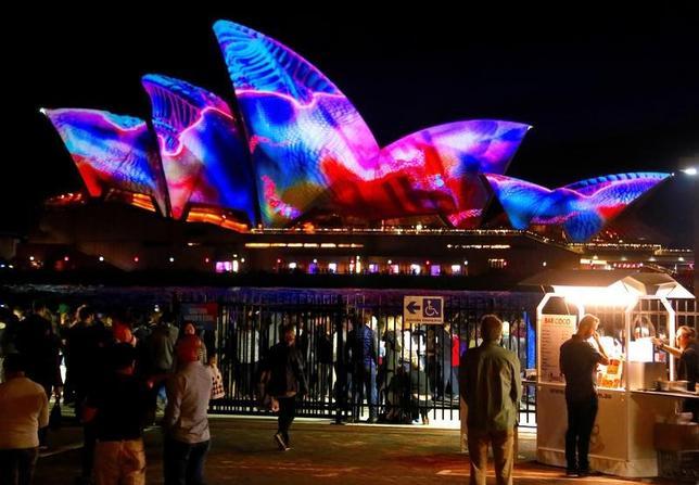 5月26日、オーストラリア東部シドニーで、光、音楽、アイデアの祭典「ビビッド・シドニー」が始まり、オペラハウス(写真)を含む市内の観光名所などが色鮮やかにライトアップされている。(2017年 ロイター/David Gray)