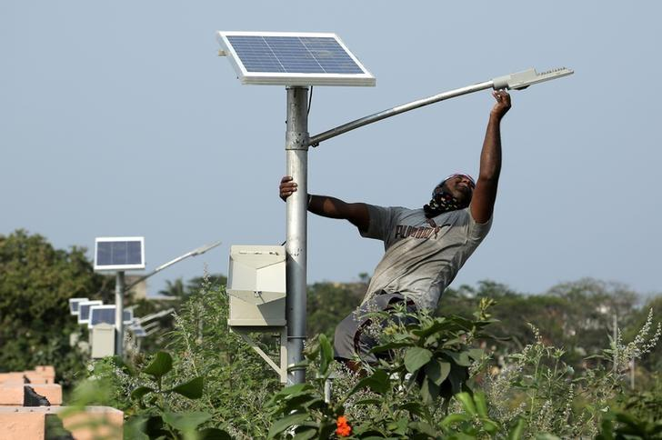 A worker installs a solar powered lamp in a public park in Chennai, India, April 11, 2017. REUTERS/Stringer/Files