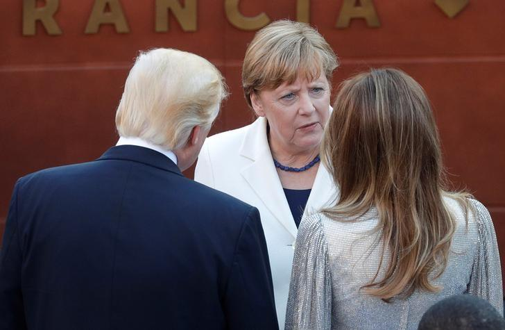 German Chancellor Angela Merkel (C) talks to U.S President Donald Trump and first lady Melania Trump as they arrive to attend a performance by the La Scala Philharmonic Orchestra in the ancient Greek theatre as part of the G7 Summit in Taormina, Sicily, Italy, May 26, 2017. REUTERS/Philippe Wojazer/Files