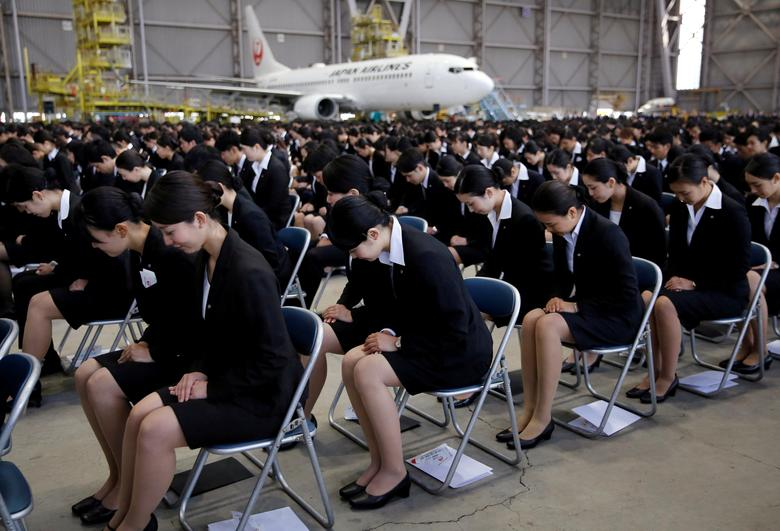 FILE PHOTO: Newly-hired employees of Japan Airlines (JAL) group bow during an initiation ceremony at a hangar of Haneda airport in Tokyo, Japan, April 3, 2017.  REUTERS/Toru Hanai/File Photo