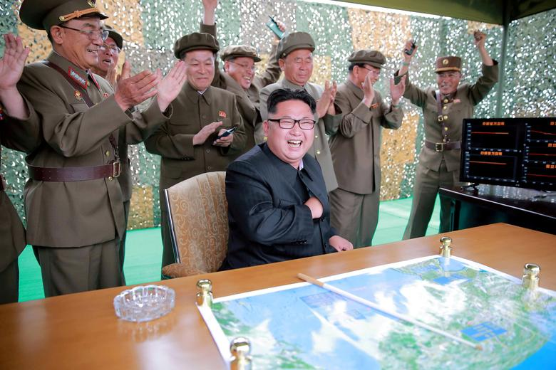 FILE PHOTO: Kim Jong Un reacts with Ri Pyong Chol (C in rear line) and Jang Chang Ha (R) during a test launch of ground-to-ground medium long-range ballistic rocket Hwasong-10 in this undated photo released June 23, 2016. REUTERS/KCNA/File Photo