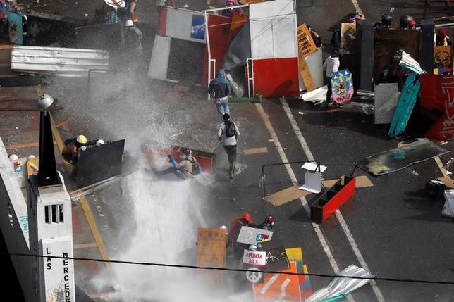 5月29日、ベネズエラの首都カラカスで、反政府デモに参加した野党指導者2人が、デモを鎮圧しようとした治安当局者にけがを負わされた。写真は放水で行進を妨げられるデモ参加者、カラカスで撮影(2017年 ロイター/Carlos Garcia Rawlins)
