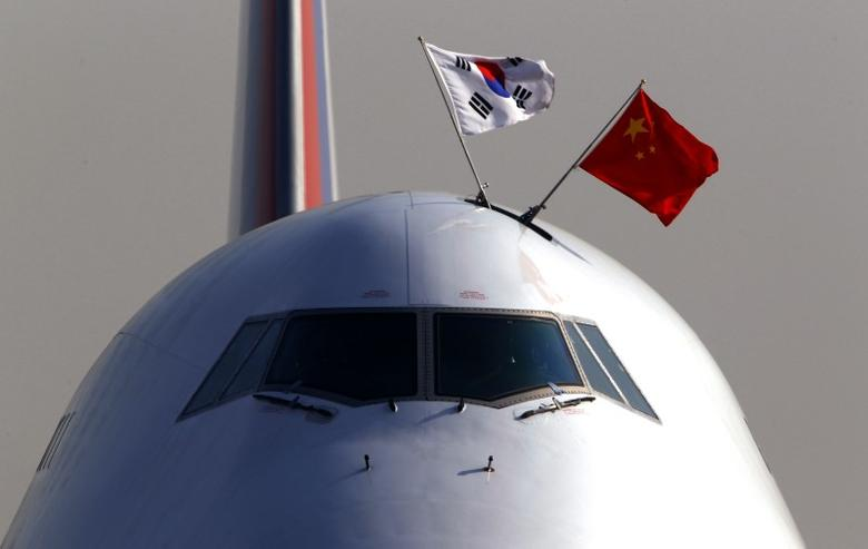FILE PHOTO - South Korean and Chinese national flags fly atop the cockpit of South Korean President Lee Myung-bak's plane as it arrives at Beijing airport January 9, 2012. REUTERS/David Gray