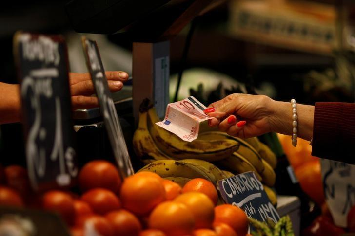 FILE PHOTO: A customer pays a vendor with a ten Euro banknote at a fruit and vegetable market in Malaga, Spain, April 19, 2012.     REUTERS/Jon Nazca/File Photo