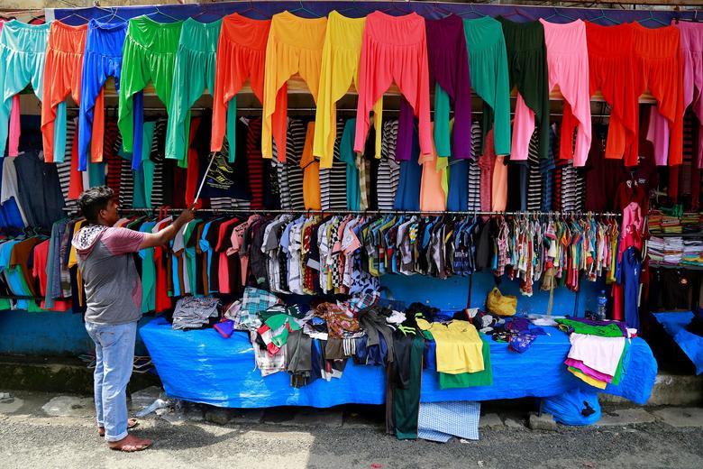 FILE PHOTO: A vendor arranges clothes at his roadside shop in Kochi, India, May 18, 2017. REUTERS/Sivaram V./File Photo