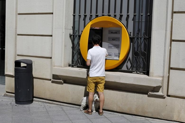 A customer with a dog uses a La Caixa automatic teller machine (ATM) in the Andalusian capital of Seville, southern Spain August 28, 2015.  REUTERS/Marcelo del Pozo