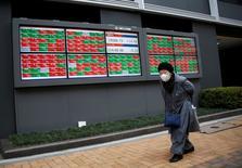 Una mujer camina frente a una tabla electrónica que muestra el precio ed las acciones en una correduría, Tokio, Japón. 20 de enero 2017. El índice Nikkei de la bolsa de Tokio cayó el martes lastrado por la fortaleza del yen, aunque un avance del peso pesado del referencial SoftBank ayudó a frenar las pérdidas. REUTERS/Kim Kyung-Hoon