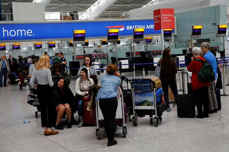 People wait with their luggage at a rebooking zone at Heathrow Terminal 5 in London, Britain May 29, 2017. REUTERS/Stefan Wermuth