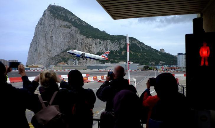 Pedestrians take photographs of a British Airways plane as it flies past the Rock of Gibraltar as they wait to cross the airport runway in the British overseas territory of Gibraltar, historically claimed by Spain, April 20, 2017. REUTERS/Phil Noble/Files