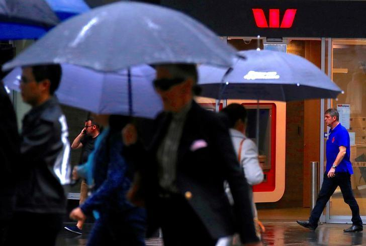 FILE PHOTO: A customer walks out of a Westpac Banking Corp branch as pedestrians holding umbrellas walk past in central Sydney, Australia, March 30, 2017. REUTERS/David Gray/File Photo
