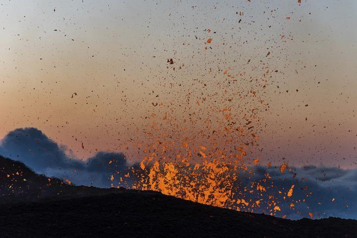 Molten lava erupts from the Piton de la Fournaise, one of the world's most active volcanoes, at dawn on the French Indian Ocean Reunion Island, August  25, 2015. The eruption which started on Monday, is the fourth one this year for the Piton de la Fournaise, sending hot jets of molten lava spewing up from the peak.  REUTERS/Gilles Adt