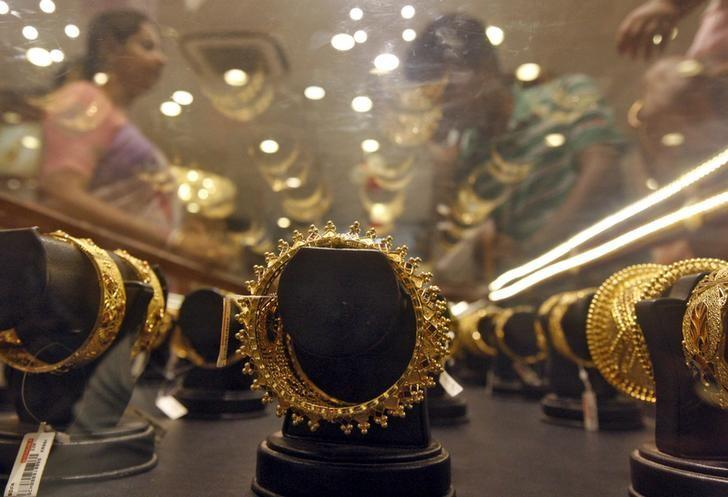 Gold bracelets are on display as a woman (L) makes choices at a jewellery showroom on the occasion of Akshaya Tritiya, a major gold buying festival, in Kolkata April 21, 2015. REUTERS/Rupak De Chowdhuri/Files