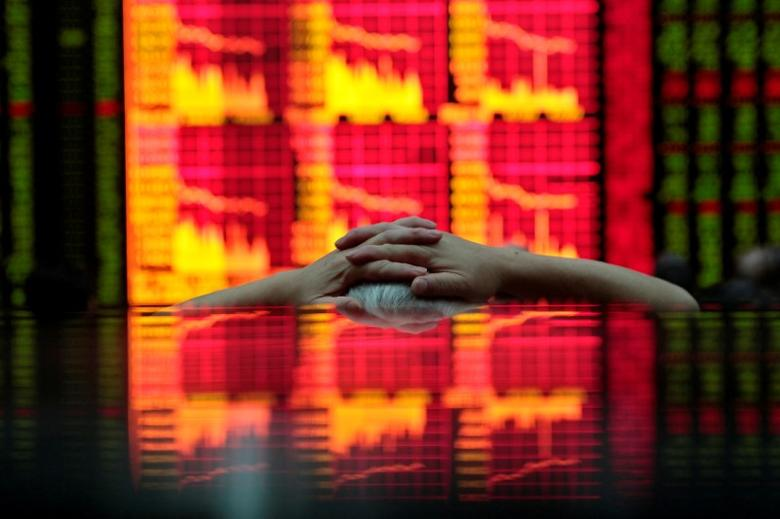 FILE PHOTO: A man looks at an electronic board at a brokerage house in Shanghai August 31, 2009.  REUTERS/Aly Song/File Photo