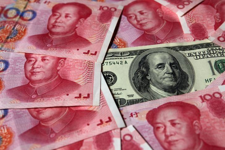 FILE PHOTO: A U.S. $100 banknote is placed next to 100 yuan banknotes in this picture illustration taken in Beijing, China, October 16, 2010. REUTERS/Petar Kujundzic/File Photo
