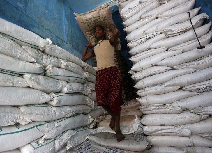 FILE PHOTO: A labourer carries a sack filled with sugar in a store at a wholesale market in Kolkata, India, February 15, 2016.  REUTERS/Rupak De Chowdhuri/File Photo
