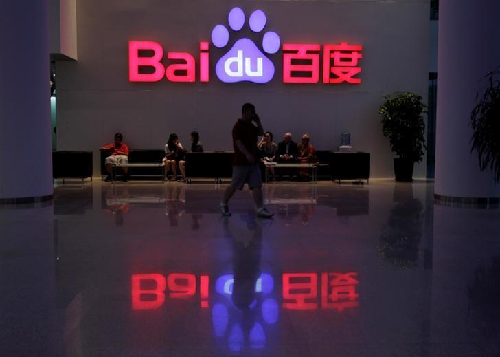 A employee uses his mobile phone as he walks past the company logo of Baidu at its headquarters in Beijing, August 5, 2010. REUTERS/Barry Huang/File Photo