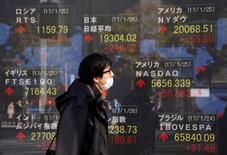 Un hombre camina cerca de un tablero electrónico que muestra el promedio del Nikkei en Tokio, Japón. 26 de enero 2017. El índice Nikkei de la bolsa de Tokio cayó el miércoles luego de que la debilidad de las acciones estadounidenses y el fortalecimiento del yen redujeron la confianza de los inversores, mientras que la caída de los precios del petróleo arrastró al sector minero.  REUTERS/Kim Kyung-Hoon