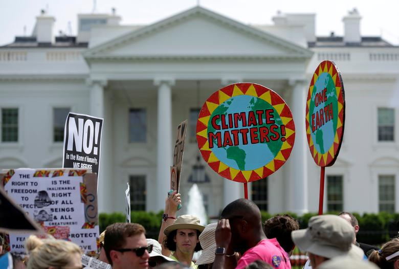 FILE PHOTO: Protesters carry signs during the Peoples Climate March at the White House in Washington, U.S., April 29, 2017.      REUTERS/Joshua Roberts/File Photo