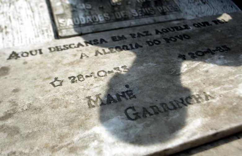 FILE PICTURE: A man casts his shadow over the grave of former Brazilian soccer player Mane Garrincha, with an inscription that's read: ''Here rests in peace the one who was the Joy of the People - Mane Garrincha,'' at cemetery in Pau Grande city near Rio de Janeiro, this pictures taken on September 23, 2004.  REUTERS/Bruno Domingos