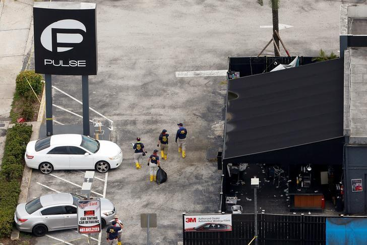 FILE PHOTO - Federal Bureau of Investigation (FBI) officials walk through the parking lot of the Pulse gay night club, the site of a mass shooting days earlier, in Orlando, Florida, U.S. on June 15, 2016.  REUTERS/Adrees Latif/File Photo