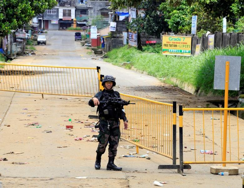 A policeman stands on guard at a main street in Sarimanok village, in Marawi city, Philippines May 31, 2017. REUTERS/Romeo Ranoco