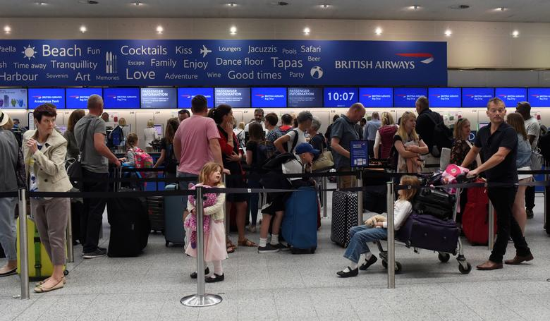 People queue with their luggage for the British Airways check-in desk at Gatwick Airport in southern England, Britain, May 28, 2017. REUTERS/Hannah McKay