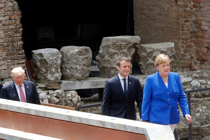 U.S. President Donald Trump (L) walks behind French President Emmanuel Macron and German Chancellor Angela Merkel (R) as they arrive for a family photo during the G7 Summit in Taormina, Sicily, Italy, May 26, 2017. REUTERS/Philippe Wojazer