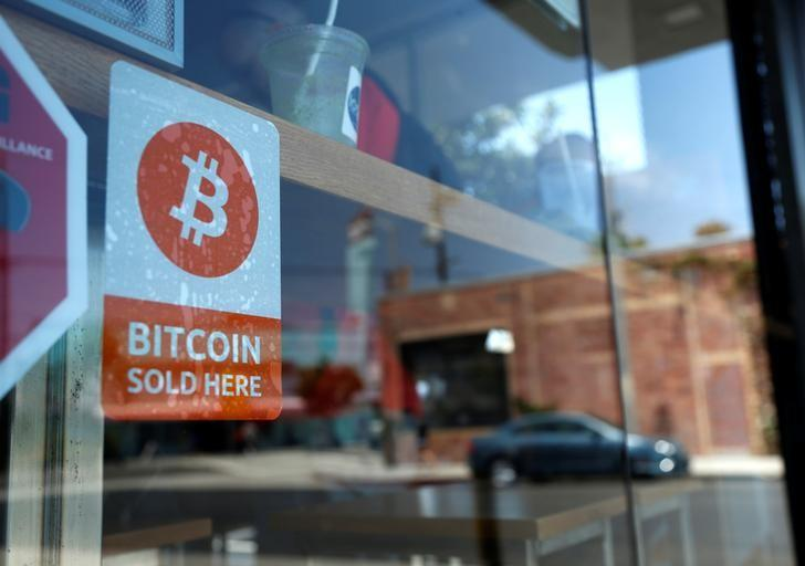 FILE PHOTO -  A bitcoin sticker is seen in the window of Locali Conscious Convenience store, where one of Southern California's first two bitcoin-to-cash ATMs began operating today, in Venice, Los Angeles, California, June 21, 2014. REUTERS/Lucy Nicholson/File Photo