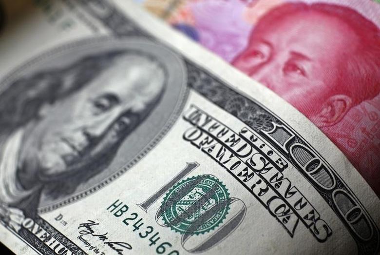 资料图片:2010年11月,百元面值的人民币纸币和美元现钞。REUTERS/Petar Kujundzic