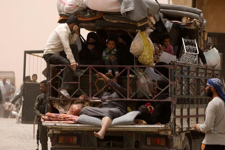 Internally displaced people who fled Raqqa city ride a vehicle with their belongings in a camp near Ain Issa, Raqqa Governorate, Syria May 19, 2017. REUTERS/Rodi Said
