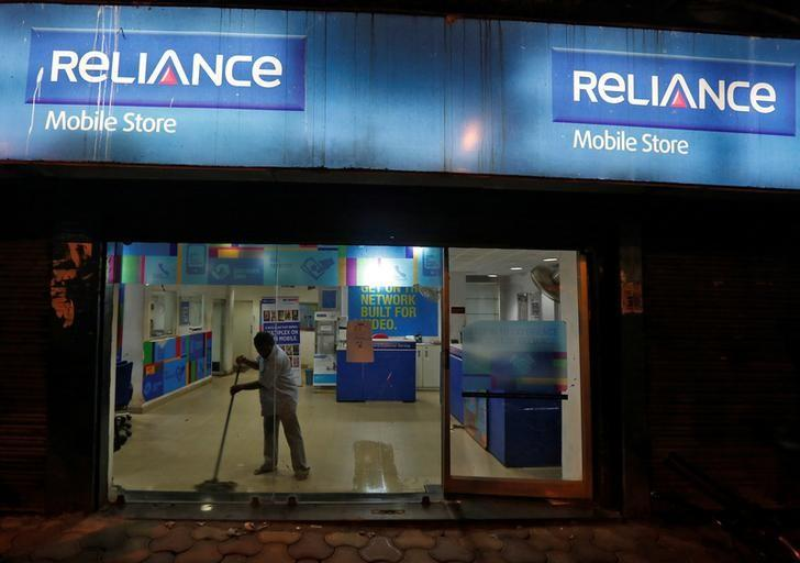 A worker cleans a mobile store of Reliance Communications Ltd, controlled by billionaire Anil Ambani, in Kolkata, India, September 10, 2016. Picture taken September 10, 2016. REUTERS/Rupak De Chowdhuri/Files