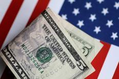 Un billete de 5 dólares con el fondo de una bandera estadounidense. 1 de junio 2017. El dólar subirá solo ligeramente a lo largo del próximo año por la disminución de las expectativas de amplios recortes de impuestos en Estados Unidos y múltiples alzas de tasas de interés de la Reserva Federal, mostró el jueves un sondeo de Reuters entre estrategas de cambio.    REUTERS/Thomas White/Illustration