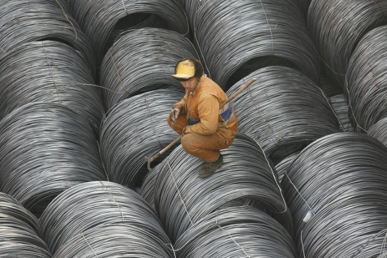A worker rests on steel to be exported at the Yingkou harbor, Liaoning province March 6, 2008. REUTERS/Stringer
