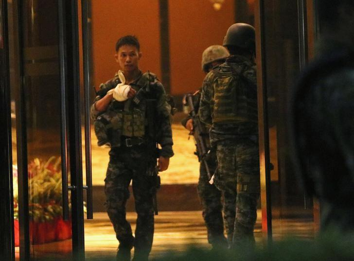 An injured policeman is seen at the entrance of a hotel after a shooting incident inside Resorts World Manila in Pasay City, Metro Manila, Philippines June 2, 2017. REUTERS/Stringer