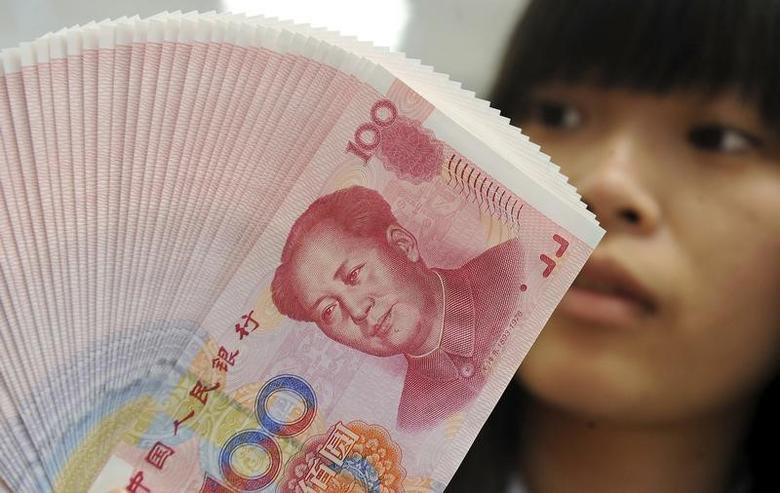 资料图片:2013年2月,台北一家银行的柜员在清点人民币纸币。REUTERS/Stringer