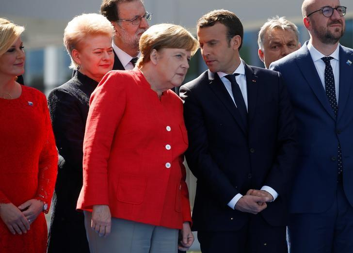 German Chancellor Angela Merkel (C) talks to French President Emmanuel Macron as they gather with NATO member leaders to pose for a family picture before the start of their summit in Brussels, Belgium, May 25, 2017. REUTERS/Jonathan Ernst