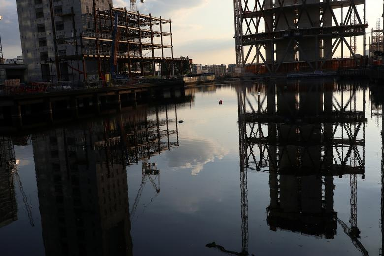 Construction work is reflected in a canal in London's Financial centre at Canary Wharf In London, Britain May 24, 2017.    REUTERS/Russell Boyce