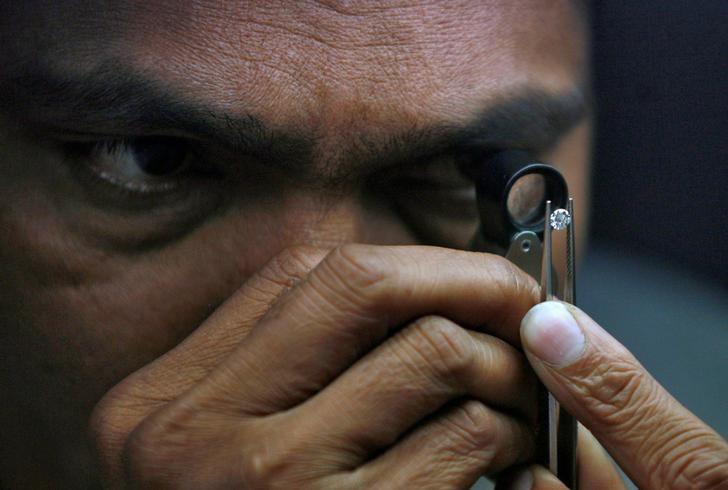 A supervisor checks the shape of a polished diamond inside the diamond processing unit at Surat, in Gujarat January 5, 2013. REUTERS/Amit Dave/File Photo