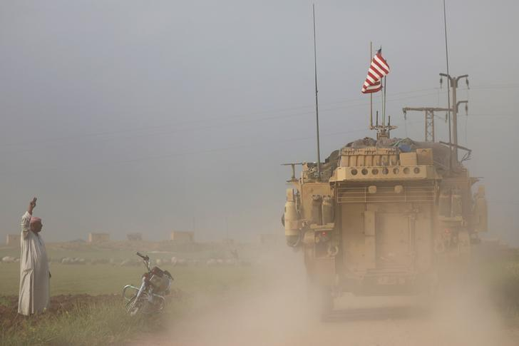 A man gestures at U.S military vehicles driving in the town of Darbasiya next to the Turkish border, Syria April 28, 2017. REUTERS/Rodi Said     TPX IMAGES OF THE DAY