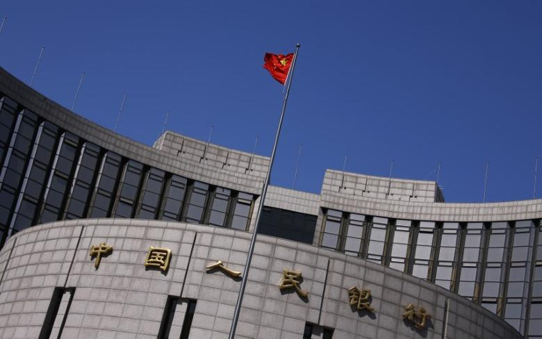 FILE PHOTO: A Chinese national flag flutters outside the headquarters of the People's Bank of China, the Chinese central bank, in Beijing, April 3, 2014. REUTERS/Petar Kujundzic