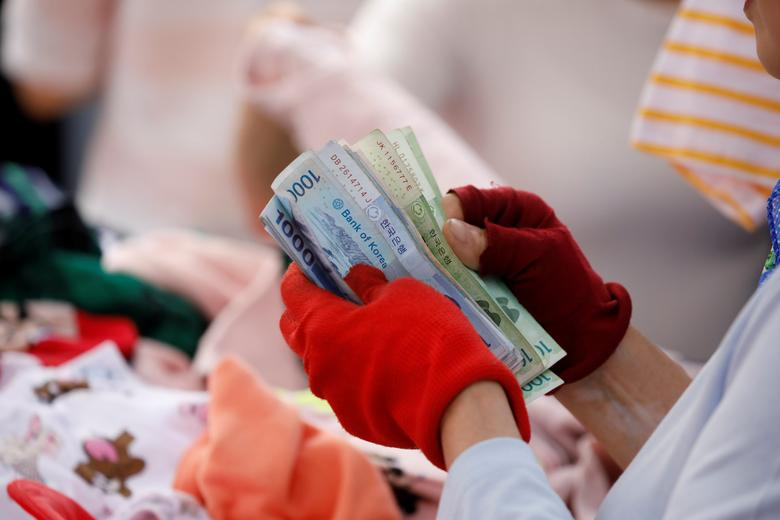 A street vendor counts his money at the Namdaemun Market in Seoul, South Korea, May 30, 2017. Picture taken on May 30, 2017.  REUTERS/Kim Hong-Ji