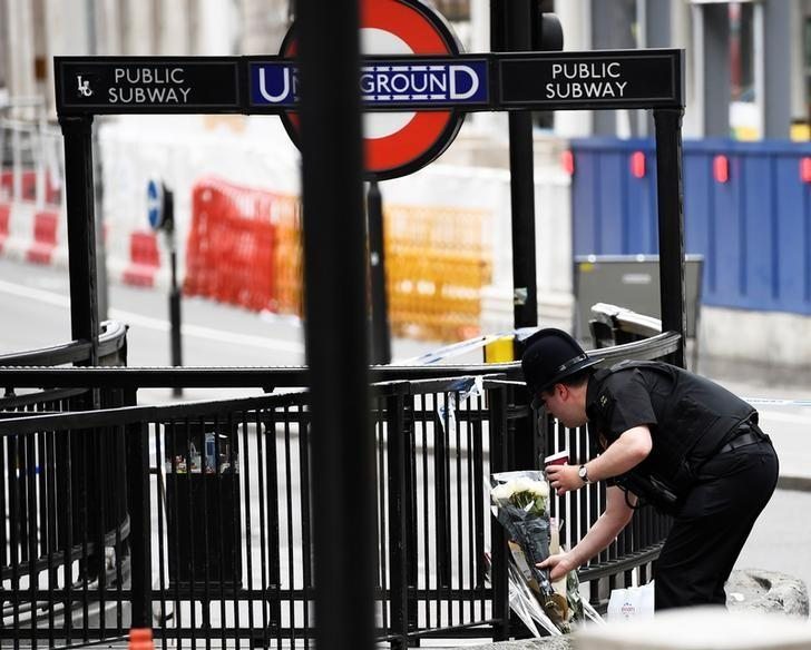 A police officer leaves flowers at London Bridge after an attack left 7 people dead and dozens injured in London, Britain, June 4, 2017. REUTERS/Dylan Martinez