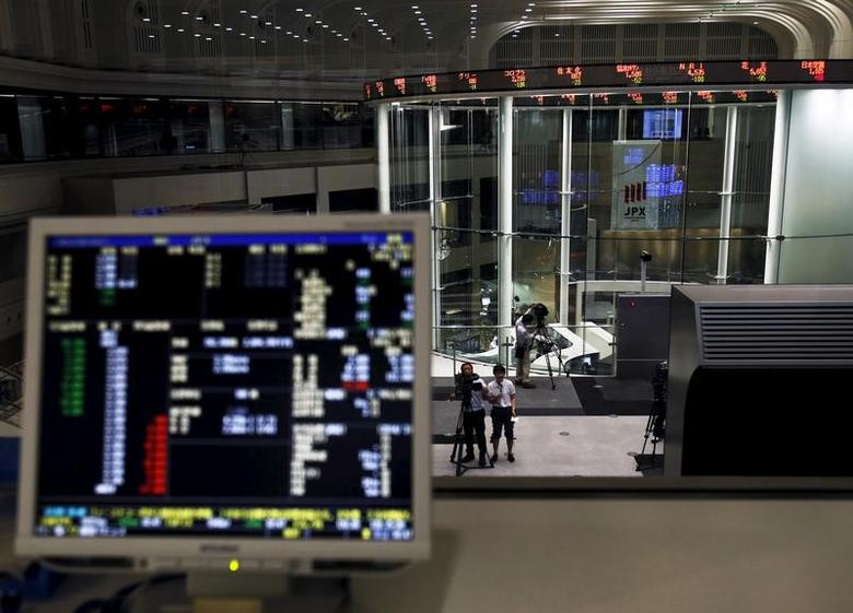 A videographer films an electronic board showing the Japan's Nikkei average and related indexes is seen next to a computer showing the market indexes at the Tokyo Stock Exchange (TSE) in Tokyo, Japan, July 9, 2015. REUTERS/Yuya Shino/Files