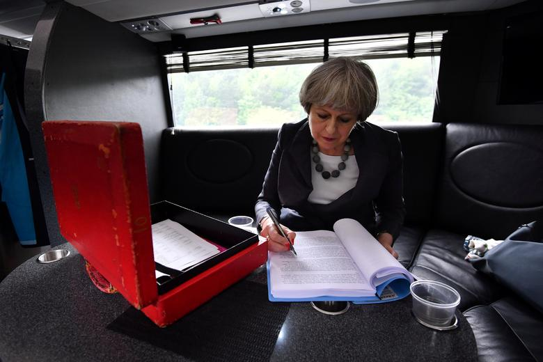 Britain's Prime Minister Theresa May works on her campaign bus as it travels through Staffordshire, June 6, 2017. REUTERS/Ben Stansall/Pool