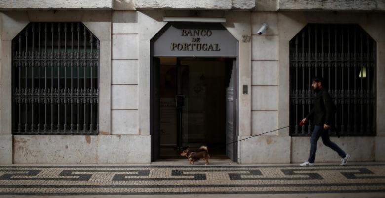 A man walks with his dog outside Bank of Portugal in downtown Lisbon, Portugal, February 21, 2017.  REUTERS/Rafael Marchante