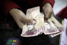 Imagen de archivo de una mujer contando bolívares en una tienda en La Guaira, Venezuela, ene 12, 2010. La segunda subasta del nuevo sistema cambiario de Venezuela, conocido como Dicom, arrojó un tipo de cambio de 2.161 bolívares por dólar, dijo el martes el Banco Central, 151 bolívares por encima del nivel de la semana pasada.  REUTERS/Jorge Silva