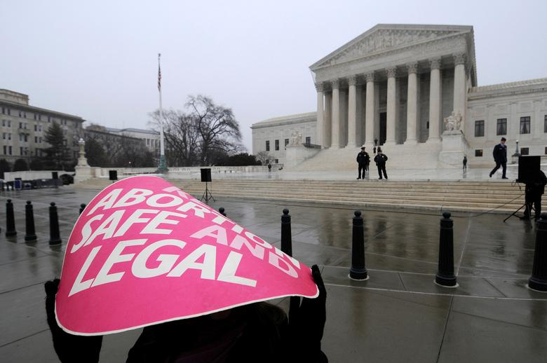 FILE PHOTO -- A woman holds a sign in the rain as abortion rights protestors arrive to prepare for a counter protest against March for Life anti-abortion demonstrators on the 39th anniversary of the Roe vs Wade decision, in front of the U.S. Supreme Court building in Washington, January 23, 2012. REUTERS/Jonathan Ernst/File Photo