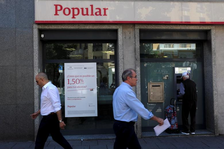 FILE PHOTO: People walk past a Banco Popular branch in Madrid, Spain, June 6, 2017. REUTERS/Juan Medina