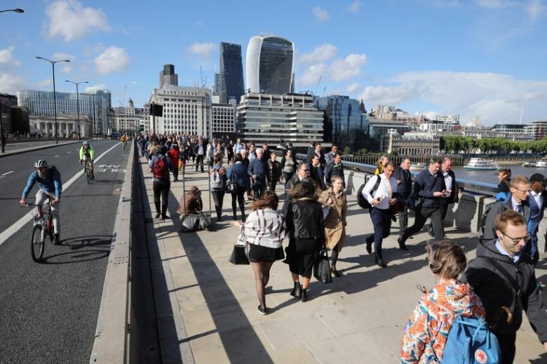 Pedestrians walk over London Bridge, past a barrier, near the recent attack on London Bridge and Borough Market,, London, Britain June 6, 2017. REUTERS/Marko Djurica